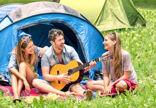 Grupo de melhores amigos cantando e se divertindo acampando juntos