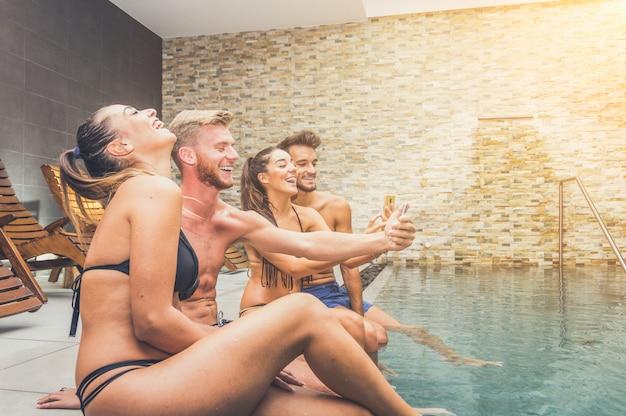 Grupo de melhores amigos tomando selfie na piscina