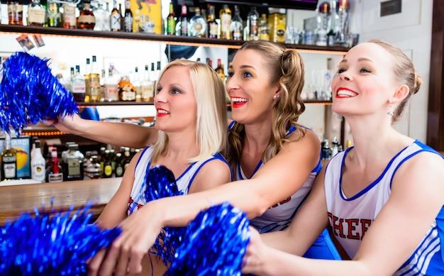 Grupo de meninas cheerleader assistindo um jogo de seu chá favorito