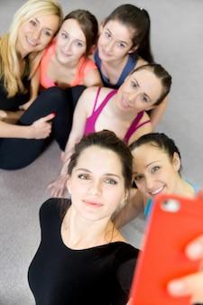 Grupo de meninas esportivas bonitas posando para selfie, auto-retrato com smartphone vermelho no ginásio desportivo