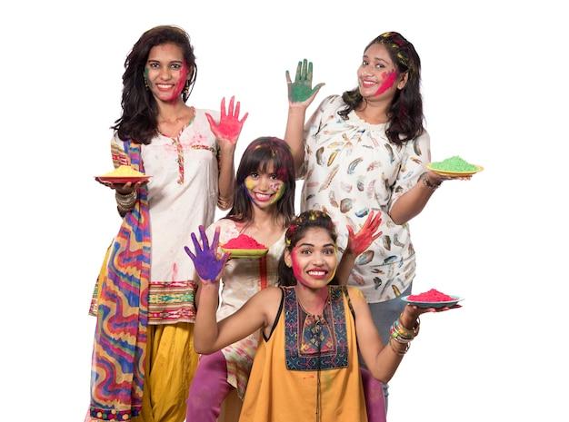 Grupo de meninas felizes se divertindo com o pó colorido no festival de cores holi