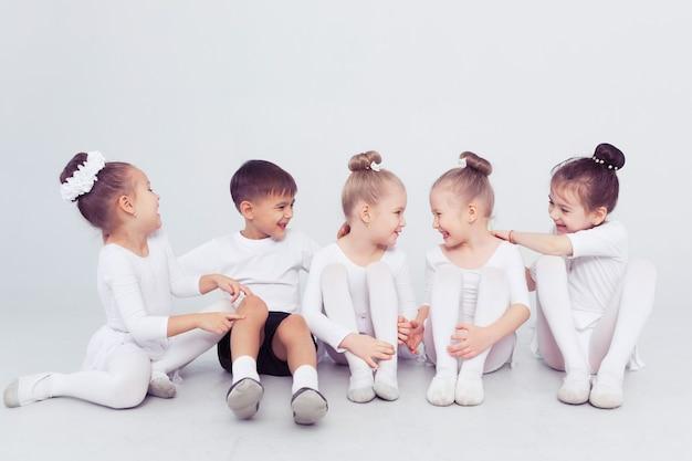 Grupo de meninos e meninas dançando em uma sala de aula ou estúdio branco, sorrindo e se abraçando