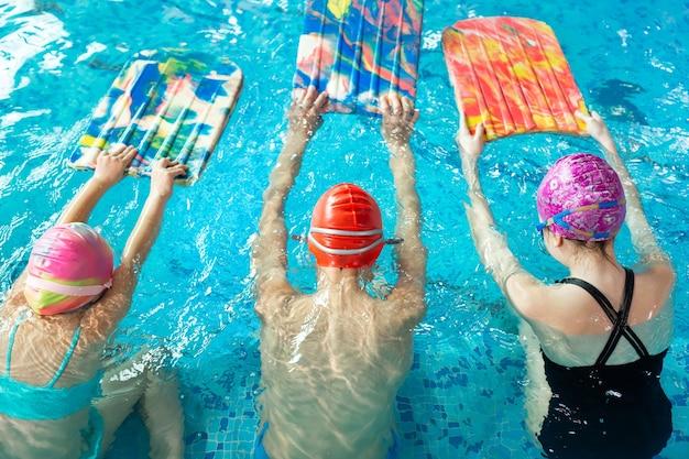 Grupo de meninos e meninas treinam e aprendem a nadar na piscina com um instrutor. desenvolvimento de esportes infantis.
