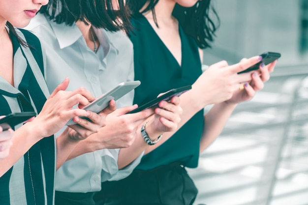 Grupo de mulher com todos no telefone ocupado com telemóvel
