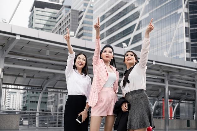 Grupo de mulher de negócios asiáticos apontando para a frente com um sorriso.