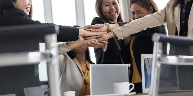 Grupo de mulher de negócios bem sucedida irreconhecível não identificada em negócios casuais usa em pé de mãos dadas empoderar como acordo de compromisso de parceria de trabalho em equipe no escritório da empresa.