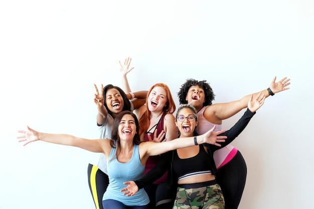 Grupo de mulheres alegres e esportivas com uma parede branca
