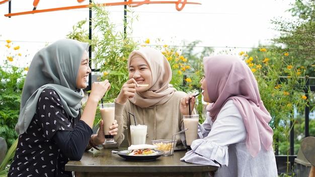 Grupo de mulheres asiáticas hijab sorrindo em um café com uma amiga Foto Premium