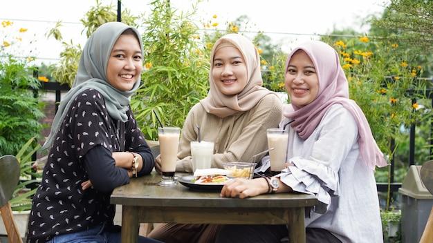 Grupo de mulheres asiáticas hijab sorrindo em um café com uma amiga