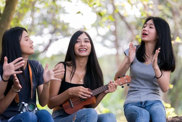 Grupo de mulheres asiáticas se divertindo acampar ao ar livre.