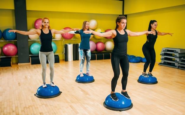 Grupo de mulheres atléticas em roupas esportivas, exercitando-se no treinamento físico. trabalho em equipe do esporte feminino no ginásio.