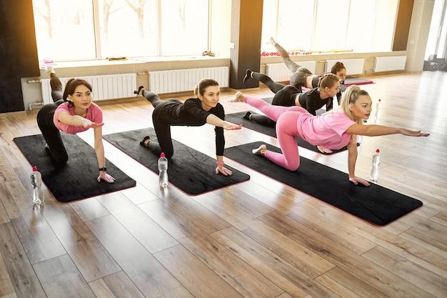 Grupo de mulheres atléticas fazendo flexões no chão e exercícios de alongamento na academia