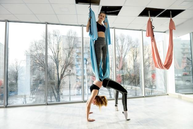 Grupo de mulheres atraentes fazendo ioga com mosca na academia