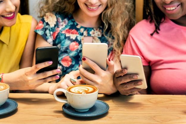 Grupo de mulheres bebendo café usando o conceito de telefone inteligente