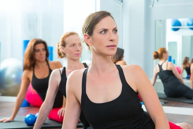 Grupo de mulheres bonitas em uma linha na aula de aeróbica