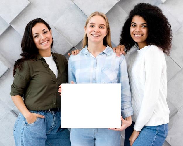 Grupo de mulheres bonitas, segurando um cartaz