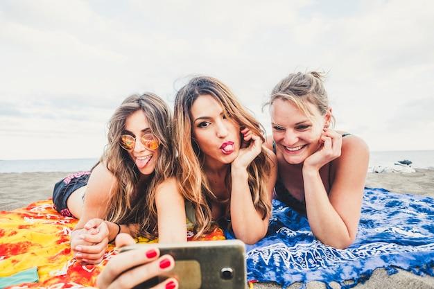 Grupo de mulheres caucasianos de três pessoas jovens bonitas e bonitas tirando fotos com smartphone na praia durante as férias e atividades ao ar livre de lazer.