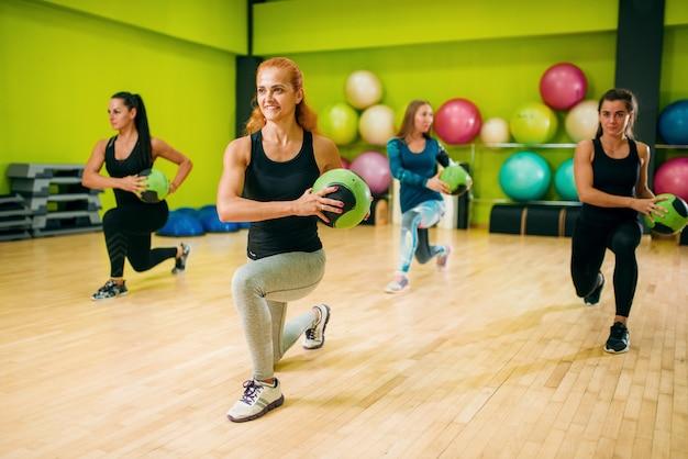 Grupo de mulheres com bolas em movimento, treino de fitness. trabalho em equipe do esporte feminino no ginásio. exercício físico, aeróbio