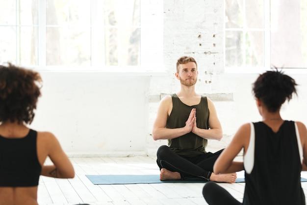 Grupo de mulheres com instrutor masculino sentado em tapetes de yoga