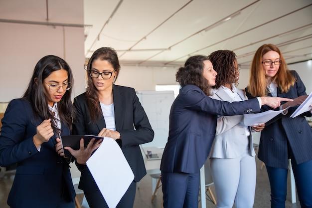 Grupo de mulheres concentradas estudando novo projeto