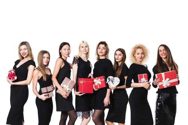 Grupo de mulheres da moda em vestido preto com presentes nas mãos isoladas. conceito de férias.