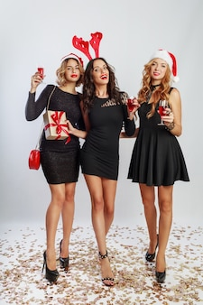 Grupo de mulheres de celebração feliz em chapéus de baile de máscaras de festa de ano novo bonito, passando um bom tempo juntos. beber álcool, dançar, se divertir. comprimento total.