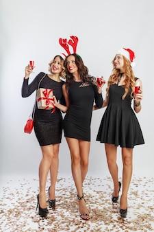 Grupo de mulheres de celebração feliz em chapéus de baile de máscaras de festa de ano novo bonito, passando um bom tempo juntos. beber álcool, dançar, se divertir em fundo branco. toda a extensão.