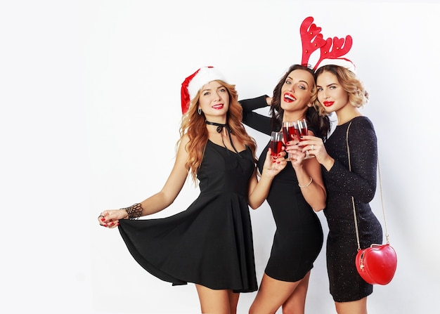 Grupo de mulheres de celebração feliz em chapéus de baile de máscaras de festa de ano novo bonito, passando um bom tempo juntos. beber álcool, dançar, se divertir em fundo branco.