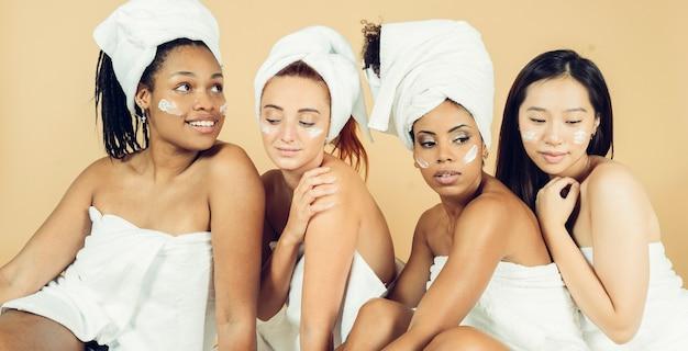 Grupo de mulheres de diferentes raças em tratamento estético em fundo amarelo