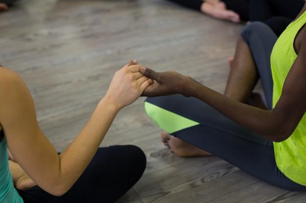 Grupo de mulheres de mãos dadas e meditando