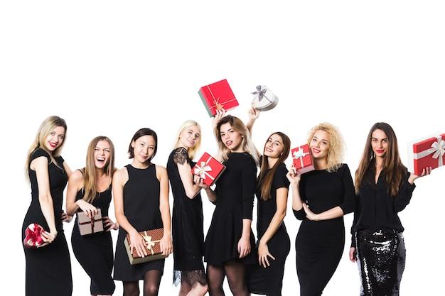 Grupo de mulheres de preto com caixas de presente nas mãos