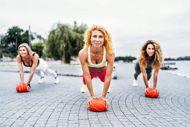 Grupo de mulheres desportivos realizando exercícios com bolas de laranja