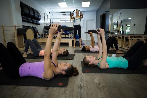 Grupo de mulheres em forma se exercitando com anel de pilates
