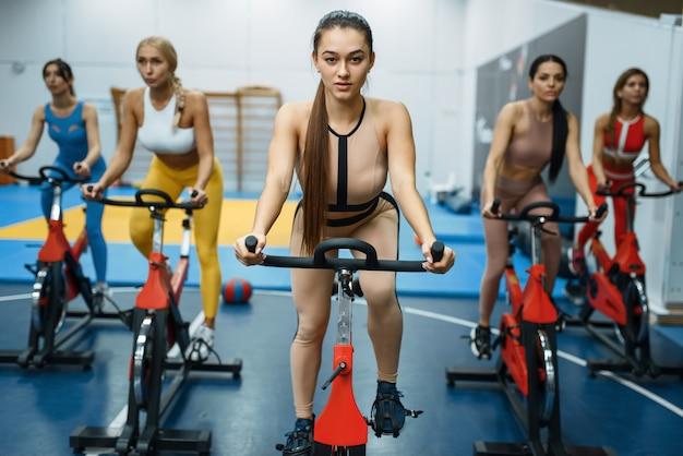 Grupo de mulheres esportivas fazendo exercícios em bicicletas ergométricas na academia