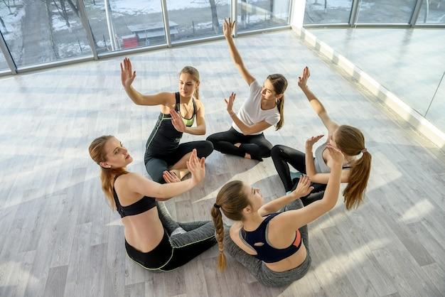Grupo de mulheres fazendo exercícios na aula de ioga