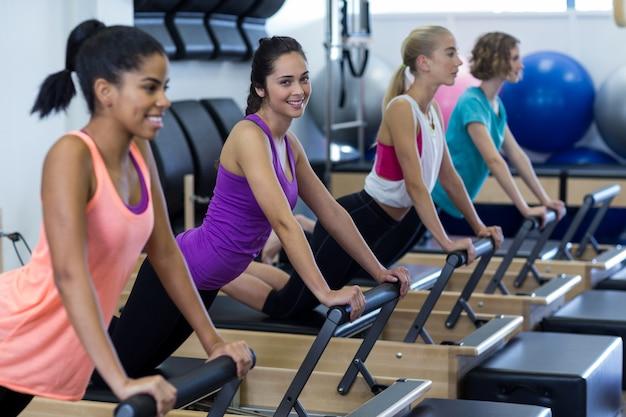 Grupo de mulheres fazendo exercícios no reformador
