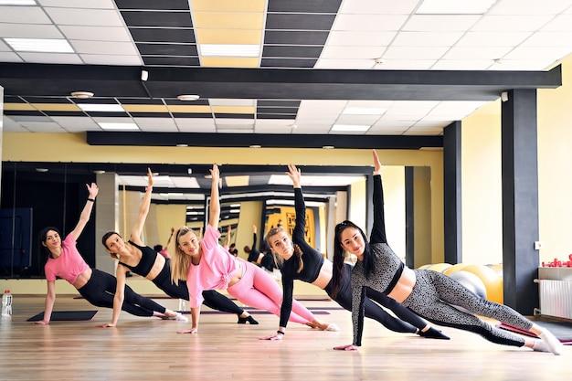 Grupo de mulheres fazendo uma prancha lateral na academia