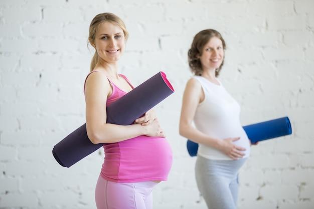 Grupo de mulheres grávidas de fitness segurando tapetes desportivos