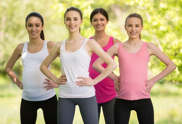 Grupo de mulheres gravidas de sorriso que fazem a ioga pré-natal.