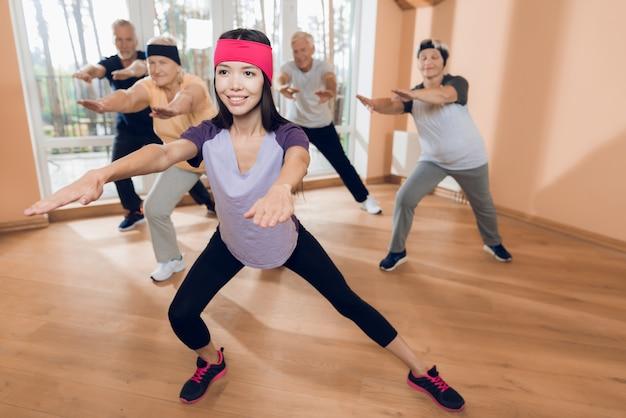 Grupo de mulheres idosas e homens fazendo ginástica terapêutica