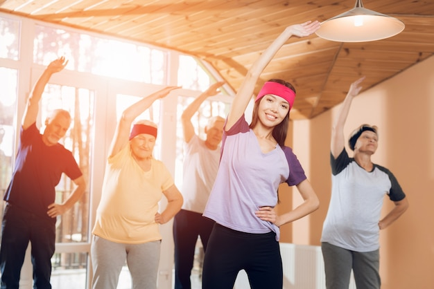 Grupo de mulheres idosas e homens que fazem a ginástica terapêutica.