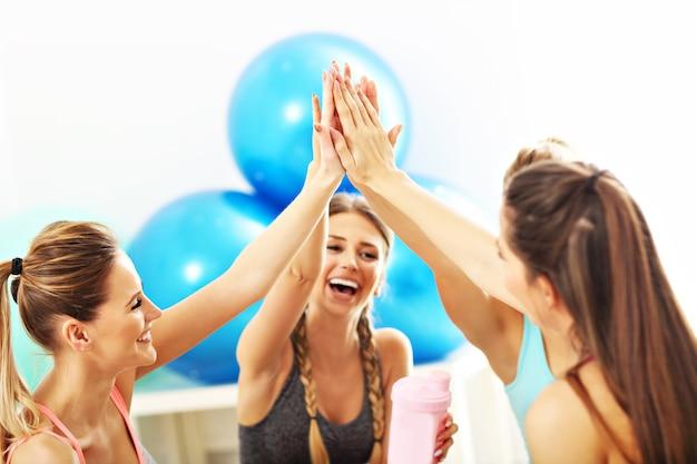 Grupo de mulheres jovens dando high five na academia após o treino
