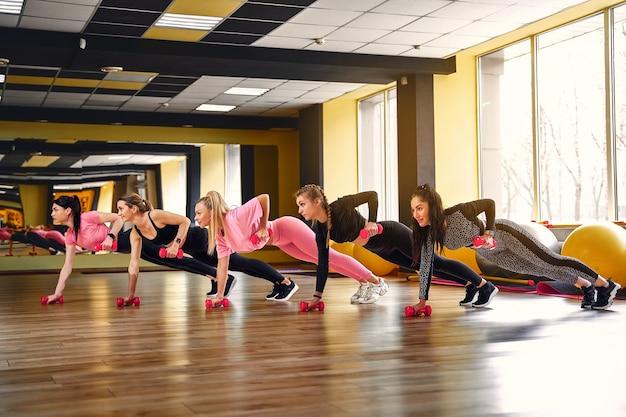 Grupo de mulheres jovens fazendo prancha em halteres juntos na academia