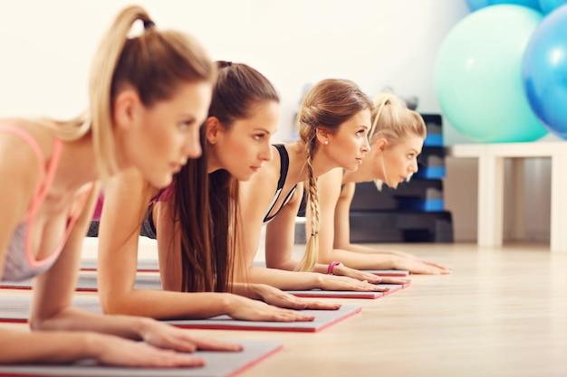 Grupo de mulheres jovens fazendo prancha juntas no ginásio