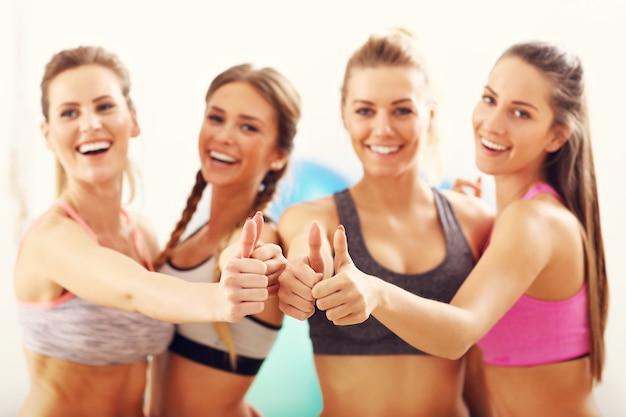 Grupo de mulheres jovens mostrando sinais de ok na academia após o treino