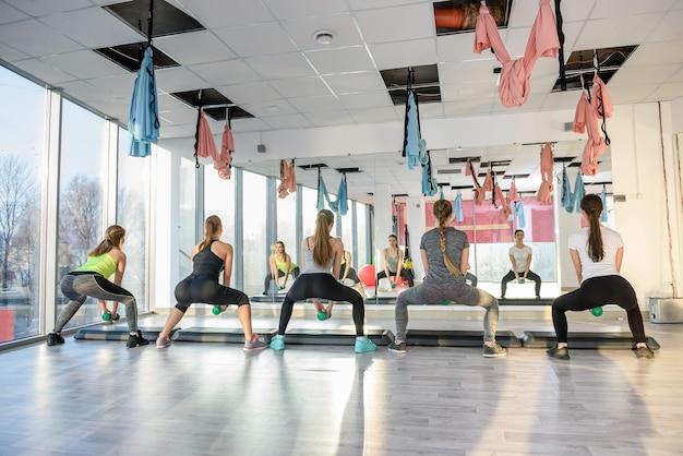 Grupo de mulheres jovens treinando na academia com halteres