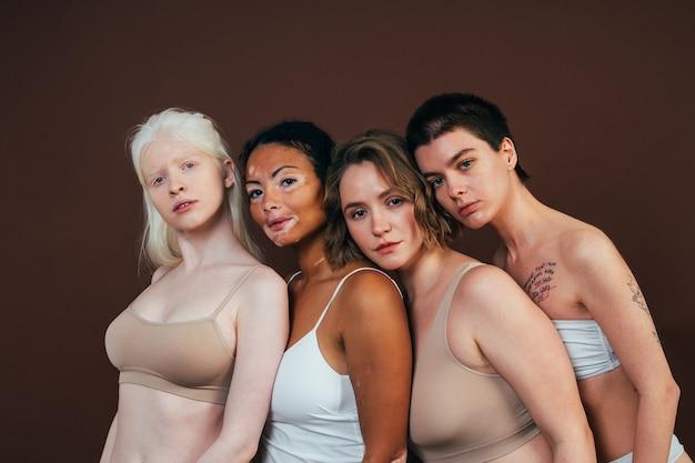 Grupo de mulheres multiétnicas com diferentes tipos de pele posando juntas em estúdio Foto Premium