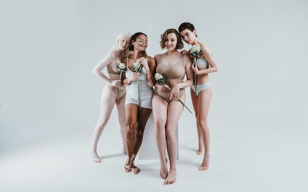 Grupo de mulheres multiétnicas com diferentes tipos de pele posando juntas no estúdio. conceito sobre o corpo