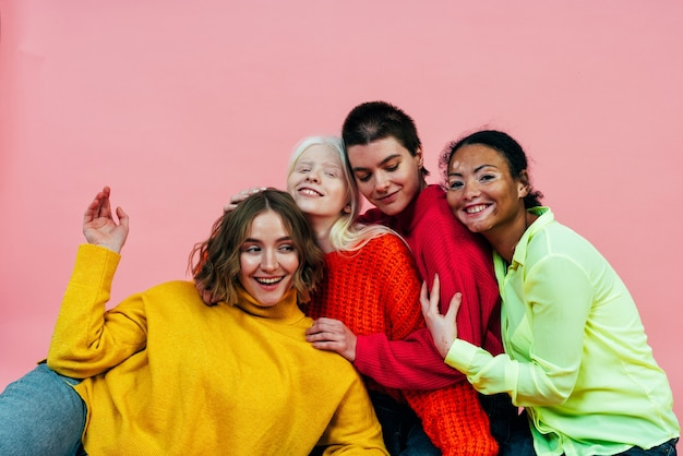 Grupo de mulheres multiétnicas com diferentes tipos de pele posando juntas no estúdio. conceito sobre o corpo Foto Premium