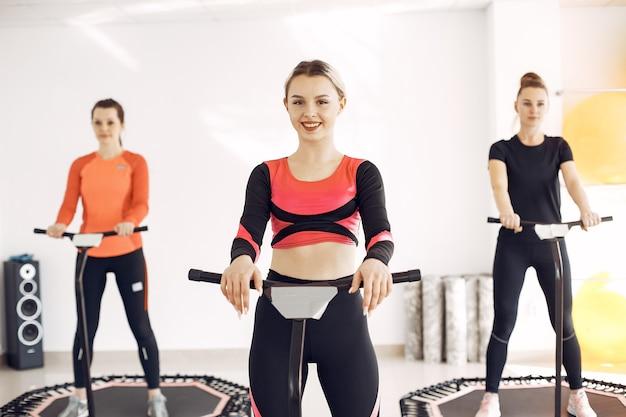 Grupo de mulheres na cama elástica esportiva. treino de fitness.